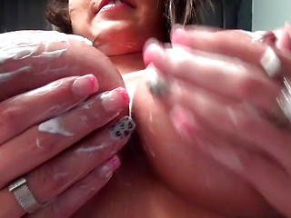 Busty Nikki Sims gripping on her tits covered in lotion