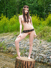 Amazing teen chick with lovely dark hair and impressive C-cup boobs posing on a big stump. - Erotic and nude pussy pics at GirlSoftcore.com
