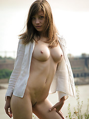 Delectable girl demonstrating splendid breasts and groomed cunt outdoor against the dike.