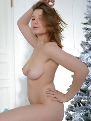 Magnificent busty charmer showing off her appetizing nude body near the Christmas tree. - Erotic and nude pussy pics at GirlSoftcore.com