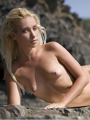 Breathtaking view of a nude blonde with carefree poses amidst the steep, rocky terrain.