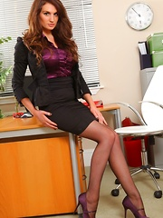 Saucy secretary in a tight black mini skirt suit and stockings.