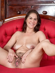 Kaysy strips off dress and lingerie on red chair - Erotic and nude pussy pics at GirlSoftcore.com